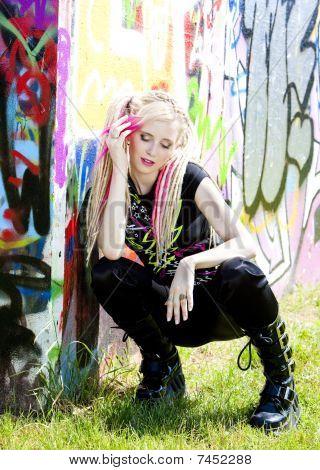 mulher sentada no muro de graffitti