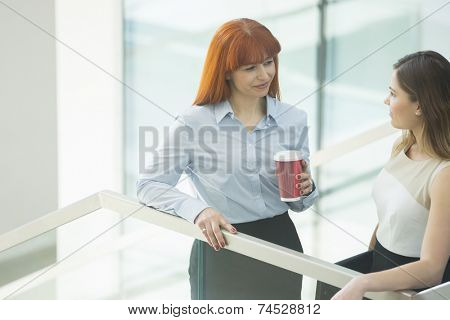 Businesswomen conversing while having coffee in office