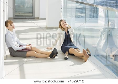 Tired businesswoman relaxing at office hallway