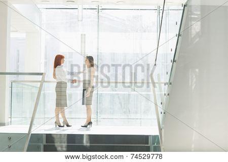 Full-length of businesswomen shaking hands in office