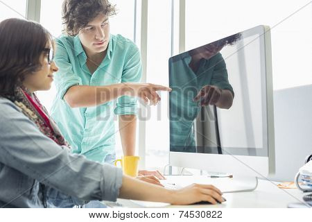 Creative businessman showing something to colleague on desktop computer in office