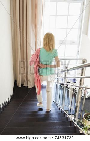 Rear view of woman wearing jacket while moving down steps at home