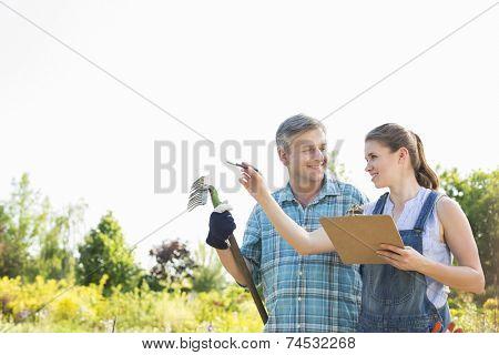 Happy female supervisor explaining something to gardener at plant nursery