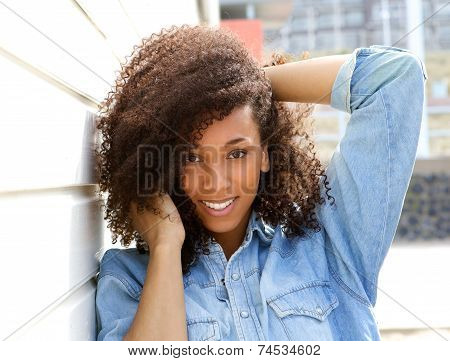 African American Woman Smiling Outdoors With Hand In Hair