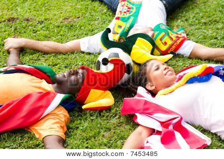 group of sports fans lying on the field