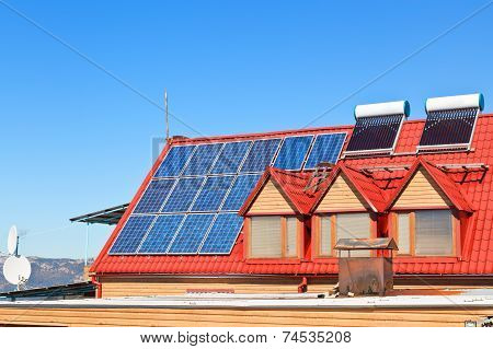 Solar Batteries And Heaters On House Roof