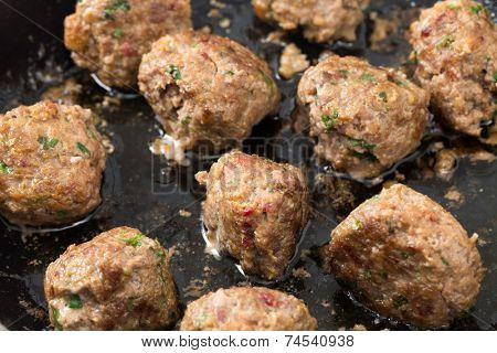 Homemade meatballs in a frying pan after cooking