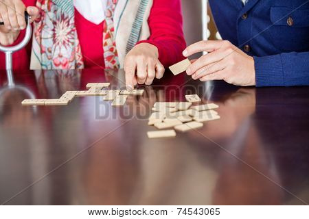 Cropped image of grandmother playing dominoes with grandson in nursing home
