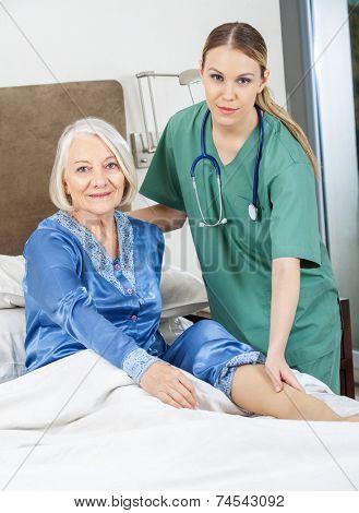 Portrait of female caretaker checking senior woman's leg in bedroom at nursing home
