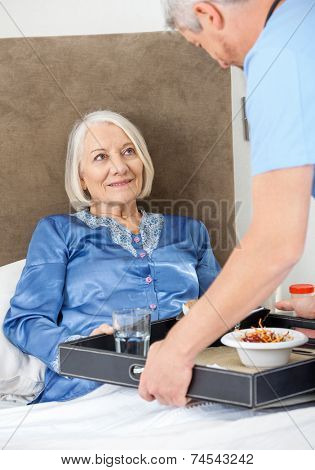 Male caretaker serving breakfast to happy senior woman on bed in nursing home