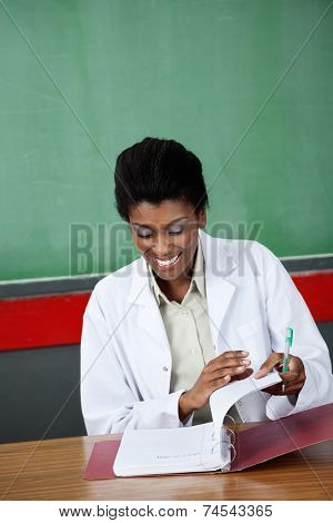 Happy young female teacher reading paper in binder at desk in classroom