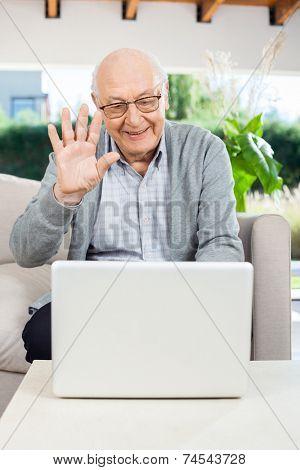 Cheerful senior man waving while video chatting on laptop at nursing home porch