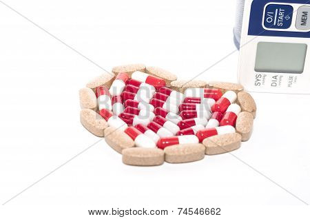Blood pressure monitor, heart made of colourful tablets on a white background