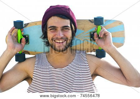 Handsome skateboarder, smiling at the camera, holding a skateboard behind his head.