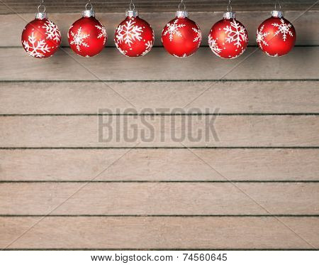 Red christmas baubles with white stars on wooden background