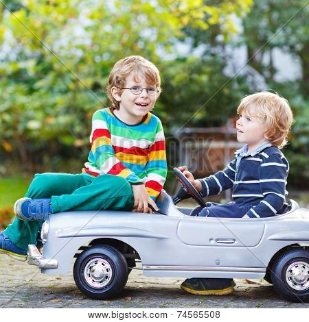 Two Happy Kids Playing With Big Old Toy Car In Summer Garden, Outdoors