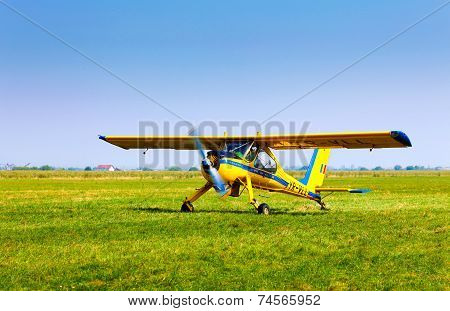 Retro Yellow Airplane On A Green Grass Field Preparing To Take Off