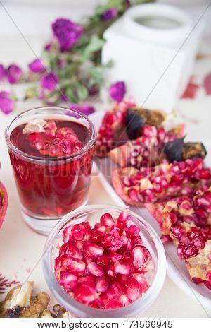 a piece of a pomegranate, a glass of pomegranate juice