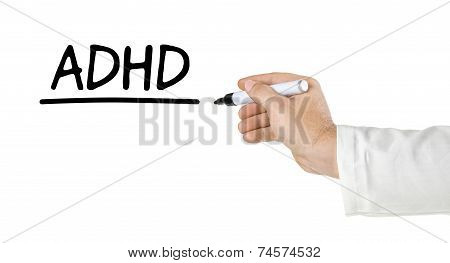 Hand with pen writing the word ADHD