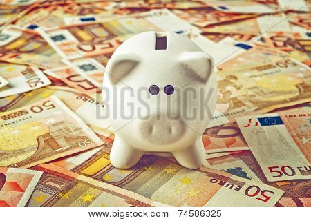 Piggy Coin Bank On Fifity Euro Pile