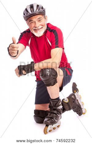senior man goes inline skating and shows thumbs up