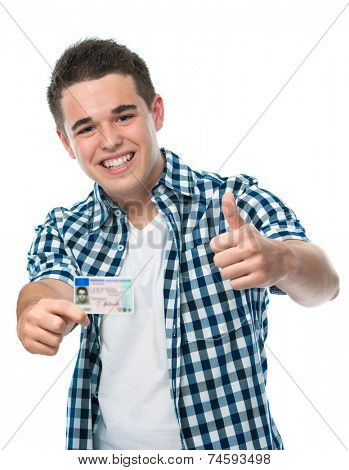 happy teenager showing his driving license