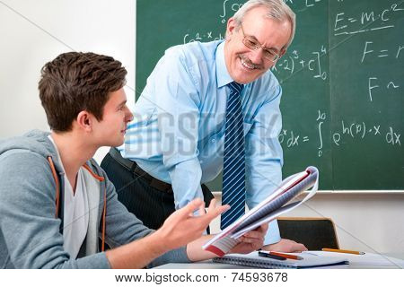 male student with a teacher in classroom