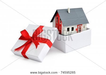 Model of a house in gift box with red ribbon
