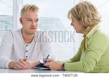 Teenager having a  therapy session while therapist is taking notes