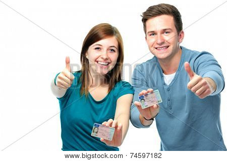 happy teens showing their driving license isolated over white