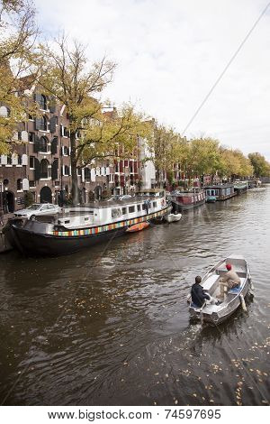 Small Boat Passing Houseboats In Brouwersgracht