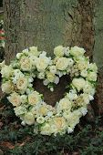 stock photo of sympathy  - Heart shaped sympathy flowers near a tree - JPG
