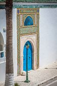 foto of stud  - Blue door with black studs and stone ornament at doorway in Tunisia - JPG