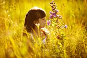 foto of beatitudes  - Happy little girl smelling a flower in the field - JPG