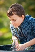 stock photo of drinking water  - Little boy drinking water from a sprinkler in a park - JPG