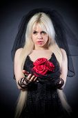 image of grief  - black widow in grief with flowers with a veil on a black background - JPG