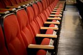 stock photo of stage decoration  - Oblique view over a row of red theatre seats at a movie theatre - JPG