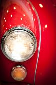 Постер, плакат: Close Up Of Headlight Of Red Classic Car