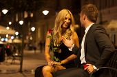 stock photo of night gown  - A beautiful elegant couple having a funny conversation on a bench  - JPG