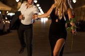 image of boys night out  - An elegant couple holding hands when running on a date at night - JPG