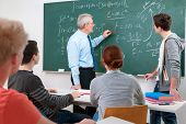 stock photo of tutor  - Teacher with a group of high school students in classroom - JPG