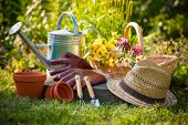 stock photo of housekeeper  - Gardening tools and a straw hat on the grass in the garden - JPG