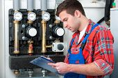 picture of hot water  - Technician servicing the gas boiler for hot water and heating - JPG