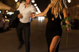 stock photo of boys night out  - An elegant couple holding hands when running on a date at night - JPG