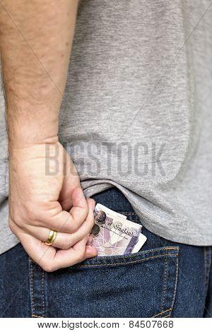 Man Puts Cash Bank Notes Into Back Pocket Of Jeans