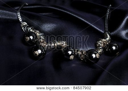 Necklace With Black Beads On Silk Background