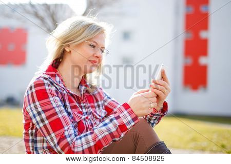 Young Businesswoman Reading Messages Outdoor
