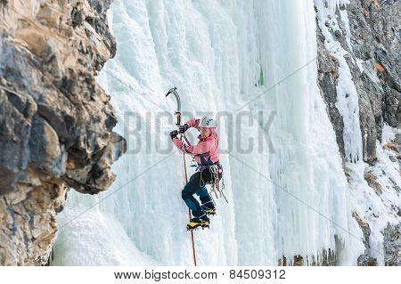 Girl Mountaineer Climbing A Frozen Waterfall And Smiling