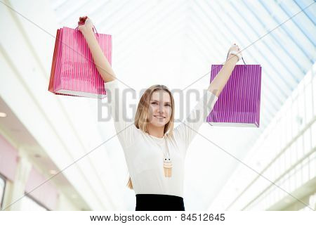 Happy Teenage Girl Pleased With Her Purchases Holding Pink Shopping Bags