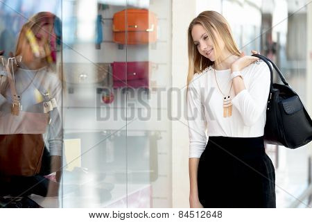 Smiling Young Woman Examining Shopwindow In Shopping Mall